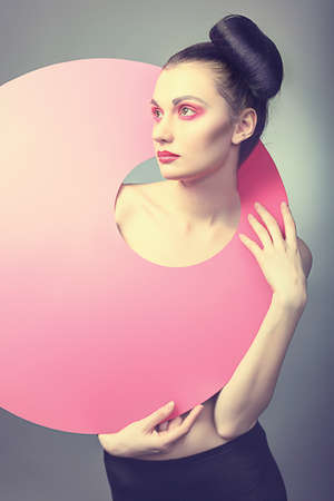 Fashion shot of an attractive model. Make-up. Shapes concept. photo