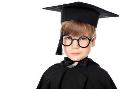 Cute little boy in graduation gown. Isolated over white background. photo