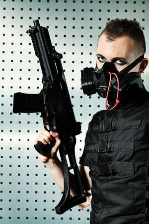 Shot of a conceptual man in a respirator holding a gun.  photo
