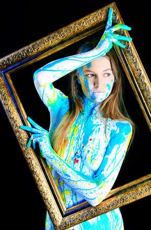 body paint: Proyecto de arte: bella mujer pintada con muchos colores vivos. Sobre fondo negro.
