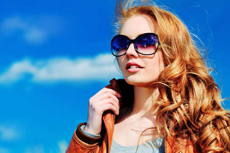 Beautiful young woman outdoors over blue sky. Stock Photo - 9620594