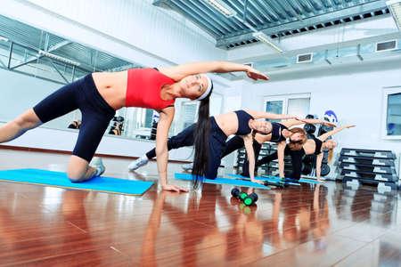 pilate: Groupe de jeunes femmes dans le centre de la salle de gym.  Banque d'images
