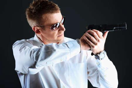 Portrait of a handsome man holding a gun. Studio shot. Stock Photo - 9631011