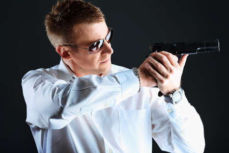 Portrait of a handsome man holding a gun. Studio shot. photo