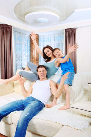 family sofa: Happy parents with their son at home. Stock Photo