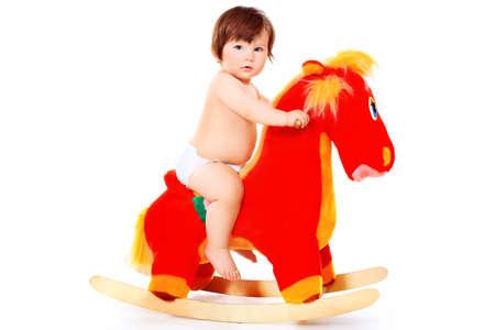 bebe sentado: Hermoso ni�o montando su caballo de juguete. Aislado en blanco.