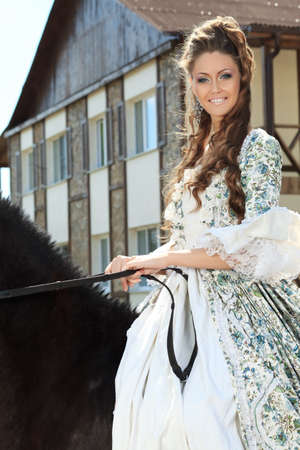 historical events: Beautiful young woman in medieval dress with a horse outdoor.