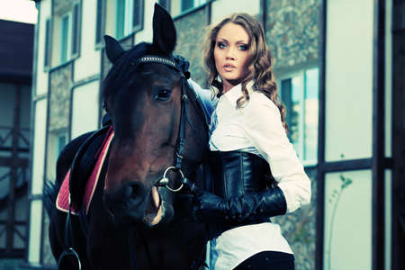 dressage: Beautiful young woman with a horse outdoor.