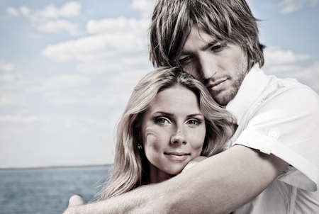 flirt: Beautiful young couple posing together over the sea.