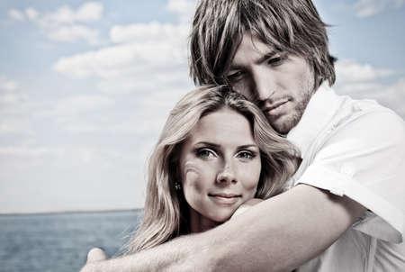 coquetear: Hermosa joven pareja posando juntos sobre el mar.