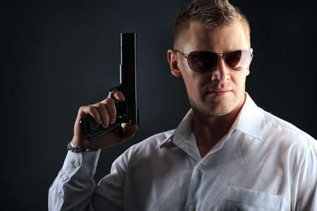 bandit: Portrait of a handsome man holding a gun. Studio shot. Stock Photo