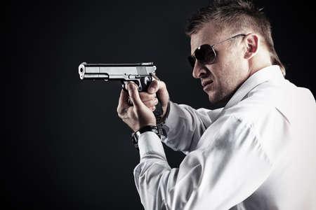 Portrait of a handsome man holding a gun. Studio shot. Stock Photo - 9685993