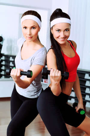 Two young sporty woman in the gym centre. photo