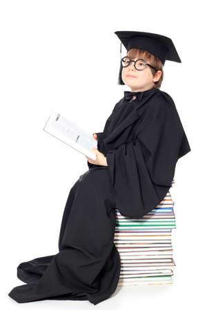 Cute little boy in a graduation gown. Isolated over white. photo