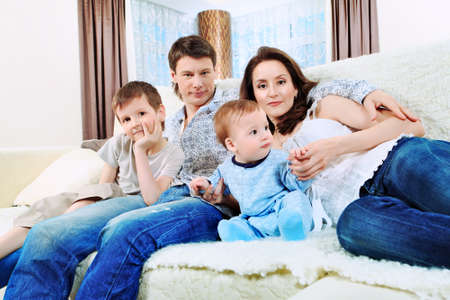 Happy parents with their two son at home. Stock Photo - 9773417