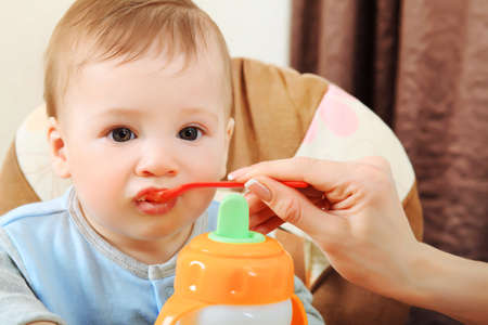 highchair: A mother is feeding her baby in the highchair at home.
