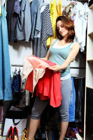 Beautiful woman looking at her clothes in a wardrobe at home. photo