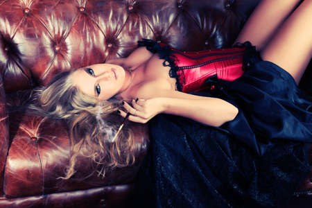lying on couch: Portrait of a sexy beautiful woman over vintage background.