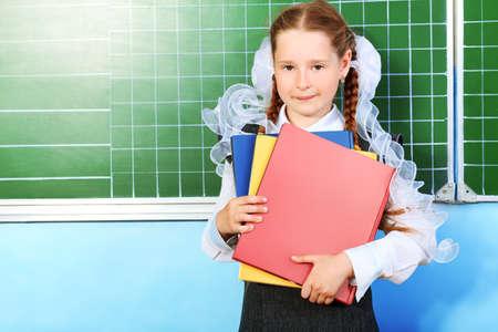 Portrait of a pretty schoolgirl in a classroom. photo