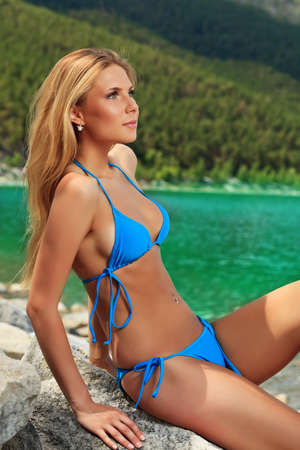 Beautiful young woman in bikini posing on a sea beach.