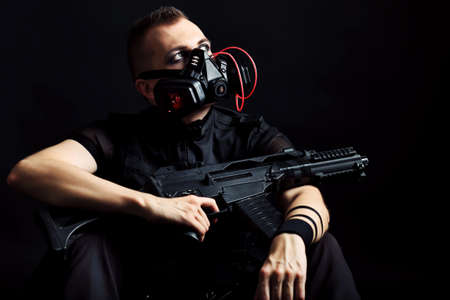 paint gun: Shot of a conceptual man in a respirator holding a gun.