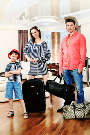 The family at home with a big suitcases is going to vacation. photo