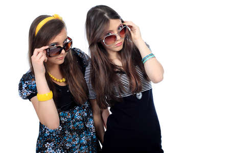 Two modern girls teenagers. Isolated over white background. photo