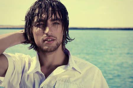 modelos hombres: Apuesto joven posando en el cielo azul y mar.