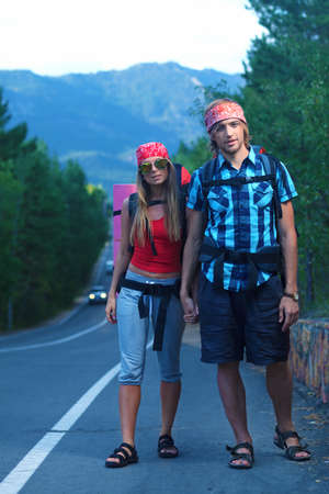 Two young people tourists hitchhiking along a road. photo