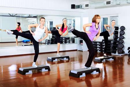 gimnasia aerobica: Grupo de mujeres j�venes en el centro del gimnasio.  Foto de archivo