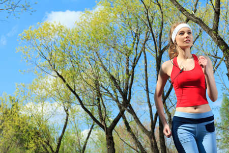Young sporty woman is jogging outdoor. photo