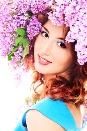 Portrait of a beautiful spring girl in lilac flowers. Isolated over white. photo