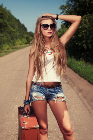 along: Pretty young woman hitchhiking along a road.