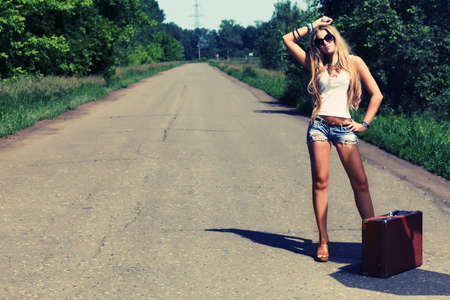 tourists stop: Pretty young woman hitchhiking along a road.