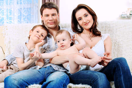 Happy parents with their two son at home. Stock Photo - 9837238