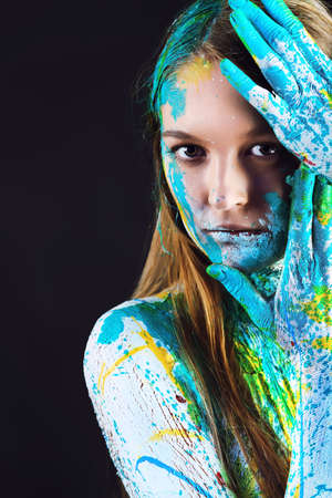 Art project: beautiful woman painted with many vivid colors. Over black background. photo
