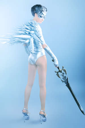 futurism: Shot of a futuristic young woman holding a sword.  Stock Photo