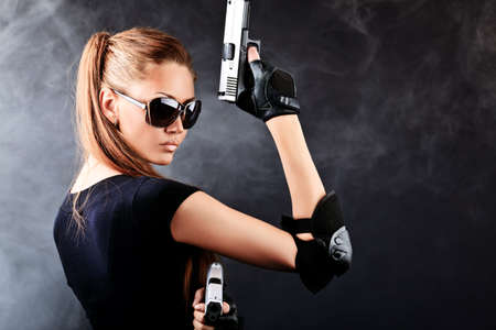 Shot of a sexy military woman posing with guns. Stock Photo - 9961303