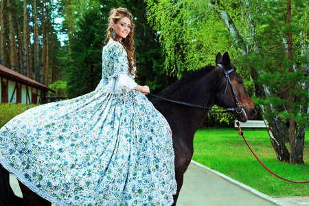 medieval dress: Hermosa mujer joven en vestido medieval con un caballo al aire libre.