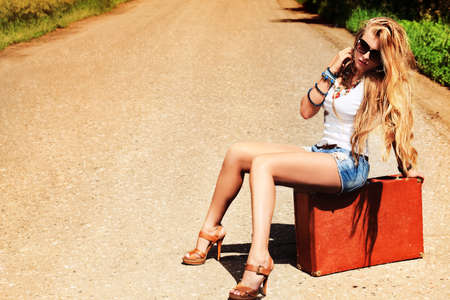 Pretty young woman hitchhiking along a road. Stock Photo - 9961489