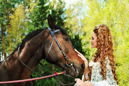 Beautiful young woman in medieval dress with a horse outdoor. Stock Photo - 9962044
