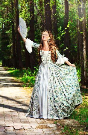 medieval dress: Beautiful young woman in medieval era dress on a sunny day outdoor. Stock Photo