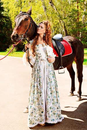 vestido medieval: Hermosa mujer joven en vestido medieval con un caballo al aire libre.