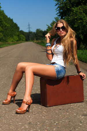 Pretty young woman hitchhiking along a road. Stock Photo - 9962123