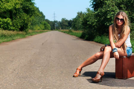 Pretty young woman hitchhiking along a road. photo