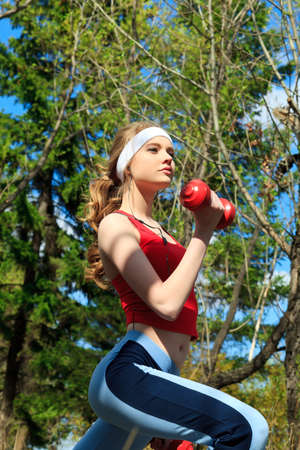 Young sporty woman is working out outdoor. photo