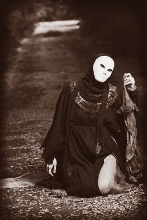 Shot of a woman in mask wearing old-fashioned dress.  photo