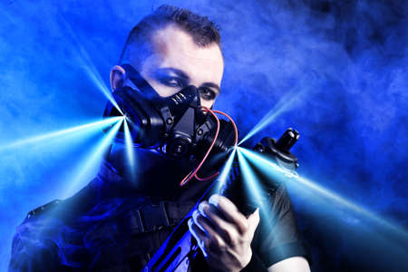 Shot of a conceptual man in a respirator holding a gun. Stock Photo - 9997396