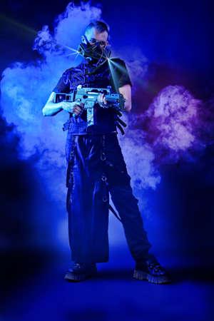 Shot of a conceptual man in a respirator holding a gun.  Stock Photo - 9997391