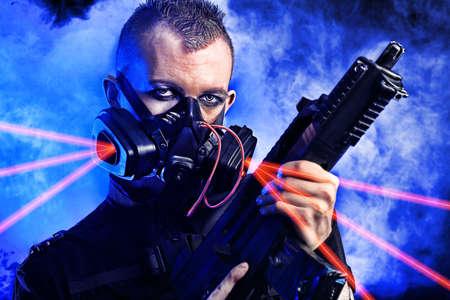 Shot of a conceptual man in a respirator holding a gun. Stock Photo - 9997392